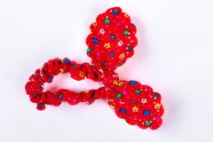Red textile hair scrunchy with a pattern of flowers. Child new elastic scrunchy with a bunny ears  on white background. Girls fashion hair accessory Stock Photo
