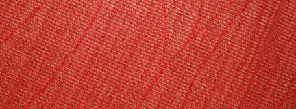 Red Textile Texture. A tight weave of red and green fibers with larger and thicker diagonal red stitches as accents Stock Photos