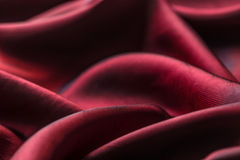Red texture. Wavy glossy silk drapery Stock Images