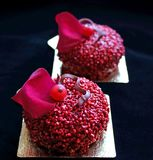 Red textured desserts with red currant berries and edible red rose petal. On black background stock photography