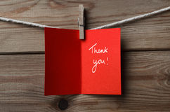 Red Thank You Card Pegged to String on Wood Background. A red greetings card, pegged on to string against wood plank background. Opened to display the words ' stock photo