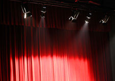 Red theater curtain over the stage and the lights overhead proje Royalty Free Stock Images