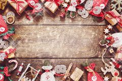 Red themed vintage rustic Christmas frame. With handcrafted ornaments, sweets, candy, advent calendar in gift bags, and cookies on a wooden background with copy Royalty Free Stock Photos