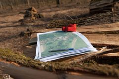 Red theodolite prism on a topographic map in woods. Map with red prism. Surveyor tools for measuring forest and land. Wooden logs in background. Detailed map Royalty Free Stock Photography