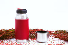 Red thermos on a white background, with dried flowers. Not isolated, selective focus.  Royalty Free Stock Images