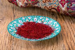 Free Red Threads And Yellow Style High Grade And Strength Of Dry Saffron Spice On Persian Turquoise Handmade Design Plate On Wooden Ta Stock Images - 106212114