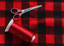 Red threat with needle and scissors on colorful fabric. View abo Stock Images