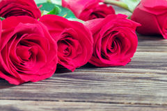 Red three roses on a wooden background Stock Images