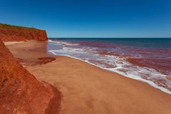 Red tide and waves against Pindan Cliffs at James Price Point. James Price Point North of Broome was the proposed site for an onshore gas processing plant stock photos