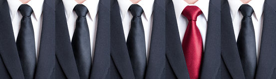 Red tie between black neckties stock photos