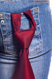 Red tie in a pocket female jeans. Red striped tie stuck in knot and being in a pocket female jeans removed close up Royalty Free Stock Photo