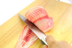 Red tilapia on chopping block . Royalty Free Stock Photos