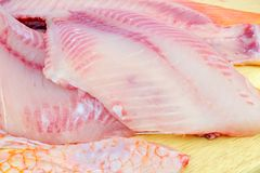 Red tilapia on chopping block . Royalty Free Stock Image