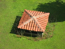 Red tile roof on a green lawn Stock Photo
