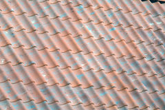 Red tile roof with green pieces Royalty Free Stock Photo
