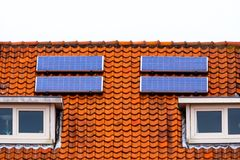 Solar panels house sky technology ecology alternative shaving economy old new roof bird tile cetamic encaustic. Red tile Roof with solar panels. New solar Royalty Free Stock Images