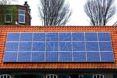 Solar panels house sky technology ecology alternative shaving economy old new roof tile cetamic encaustic. Red tile Roof with solar panels. New solar Royalty Free Stock Photos