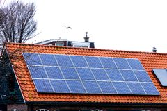 Solar panels house sky technology ecology alternative shaving economy old new roof tile cetamic encaustic. Red tile Roof with solar panels. New solar Royalty Free Stock Photography