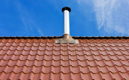 Red tile roof with a tin chimney Stock Photography