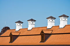 Red tile roof and white chimneys. Red tile roof of an old building with four white chimneys and two dormers on blue sky Stock Images