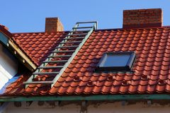 Red tile roof with window stairs and chimney. Against the blue sky stock image