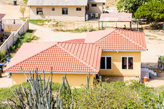 Red Tile Roof on Yellow Plaster Home Stock Images