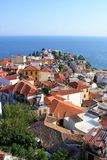 Red tile rooftops in Mediterranean town. A village on a peninsula juts out into the blue azure sea as the sun shines down on the white washed orange rooftops of Stock Images