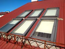 Red tiled house roof with attic windows. Roofing construction, window installation, modern architecture concept royalty free stock photo
