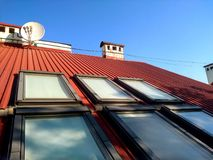 Red tiled house roof with attic windows. Roofing construction, window installation, modern architecture concept.  stock photography
