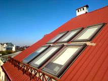 Red tiled house roof with attic windows. Roofing construction, window installation, modern architecture concept royalty free stock image
