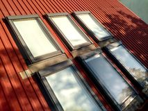 Red tiled house roof with six attic windows. Roofing construction, window installation, modern architecture concept royalty free stock photo