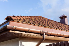 Red tiled roof with gutter and chimney Royalty Free Stock Photo
