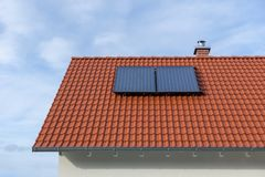Red tiled roof with solar thermal power plant. Red tiles tiled roof solar thermal power plant energy sun light warm heating water panels sky construction stock photography