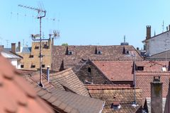 Red tiled rooftops in a town with antennae. Red tiled rooftops in a town with television and radio antennae in an elevated view against a clear blue sky stock images