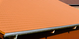 Red tiles roof with rain pipe and corrugated metal wall. Royalty Free Stock Photos