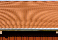 Red tiles roof with rain pipe and corrugated metal wall. Stock Images