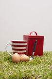 Red tin, coffee cup, two eggs and a spoon. Stock Image