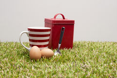 Red tin, coffee cup, two eggs and a spoon. Royalty Free Stock Photos