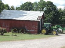 Red tin roof barn. Home of big green tractor Royalty Free Stock Photography