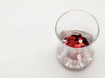 Red tinsel in glass. Red paillette in glass isolated on white background Stock Photos