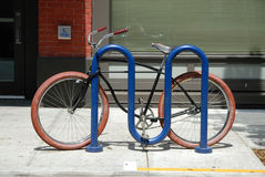 Red Tire Bicycle. Black bicycle with red tires locked to a blue railing Royalty Free Stock Image