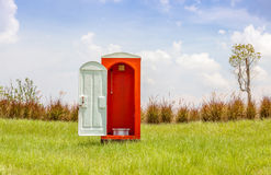 The red toilet with white door open contrast with green grass an Royalty Free Stock Photography