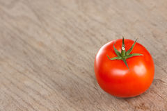 Red tomato on a brown table Royalty Free Stock Photos