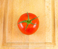 Red tomato on chopping bord Stock Image