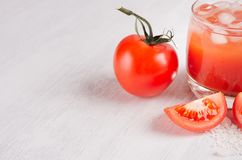 Red tomato cocktail in misted glass with juicy slice cut tomato, straw, ice, salt on soft white wood board, copy space, closeup. Red tomato cocktail in misted stock photo