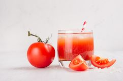 Red tomato cocktail in misted glass with juicy slice cut tomato, straw, ice, salt on soft white wood board, copy space. Red tomato cocktail in misted glass with royalty free stock photography