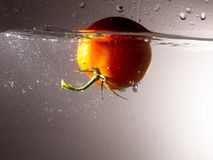 Red tomato drops in water with a spray royalty free stock photography