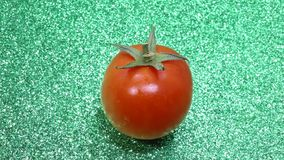 Red tomato on a green background stock footage