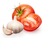 Red tomato with green leaf, half and garlic with clove Royalty Free Stock Images