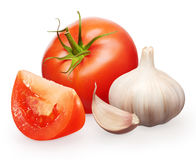 Red tomato with green leaf, slice and garlic with clove Royalty Free Stock Photo
